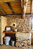 Suitcase and saucepan on wooden shelf next to stone basin in converted barn