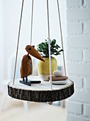A bird figure, a house plant and stones on a homemade hanging shelf