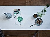 Teekanne, Farbkasten, gemaltes Pflanzenblatt, Tee und Kuchen