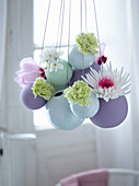 Easter arrangement of flowers in suspended spherical vases