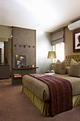 Double bed in guest bedroom in subdued shades