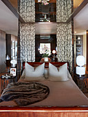 Mahogany sleigh bed in elegant bedroom with mirrored ceiling