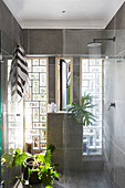 Shower area in bathroom with glass brick windows and concrete-effect walls