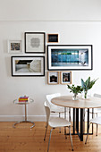 Round table, chairs and framed photos on wall in dining area