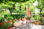 Mosaic table and metal chairs on terrace in lush garden