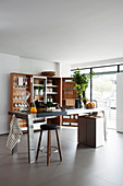 Stainless steel island counter and trunk-style folding cabinet in kitchen