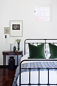 Double bed with metal frame, green pillows and console table used as bed stand