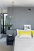 Kopfkissen mit gelbem Farbakzent auf Doppelbett im Schlafzimmer mit grau getönter Wand