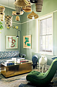 Easy chair with green upholstery, animal sculptures, coffee table and sofa in lounge with green-painted walls