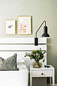 Vase of flowers on white bedside table next to bed with white-painted wooden headboard
