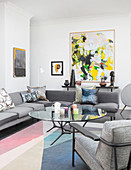 Abstract painting in living room with grey furniture and pastel colour scheme