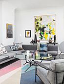Abstraktes Gemälde im Wohnzimmer mit grauen Möbeln und Pastellfarben