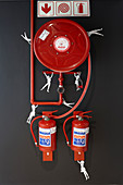 Fire extinguishers on black wall