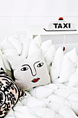 White pillow sofa with decorative pillows, in the background a taxi light as a table lamp
