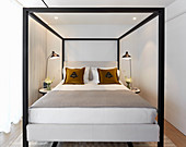 Four-poster bed with black cubist frame in small room