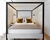 Himmelbett mit schwarzem, kubischem Rahmen im kleinen Raum