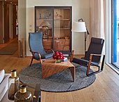 Two armchairs and engineered wooden table on round rug in front of display case