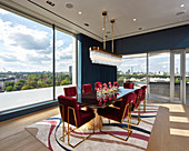 Red velvet chairs with gilt frames in dining room with panoramic view of city
