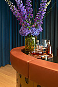 Vase of blue flowers and tray of bottles on bar