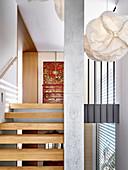 Designer-Pendelleuchte im Treppenhaus mit Stufen aus Eichenholz und Betonstütze
