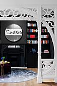 Durchgang mit Holzschnitzerei, Blick auf schwarze Wohnzimmerwand mit Kamin und rundem Spiegel