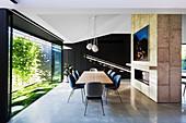 Mittelwand mit eingebautem Kamin, davor langer Esstisch mit Stühlen und Glasfront