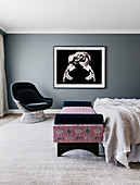 Upholstered armchairs, daybed at the end of the bed and large-format photography on a gray wall in the bedroom
