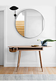 Designer wall table under a round mirror and black wall lamp