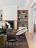 Classic chairs and coffee table with orchid in front of built-in fireplace and open wooden shelf