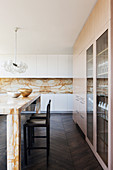 Einbauschrank mit Vitrineneinsatz, Kücheninsel und Spritzschutz aus Marmor in eleganter, offener Küche