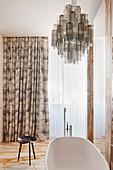Badezimmer mit Marmor-Fliesenboden und Kronleuchter aus Muranoglas über der Badewanne