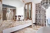 Badezimmer mit Marmor-Waschtisch, Marmor-Fliesenboden und Kronleuchter aus Muranoglas über der Badewanne