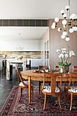 Ovaler Esstisch mit Stühlen unter Vintage Lampe, im Hintergrund Kücheninsel aus Marmor