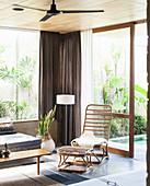 Liegestuhl mit Fell und Fusshocker vor Glastür