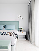 Custom-made double bed with mint green headboard, bedside table and wall lamp in the bedroom