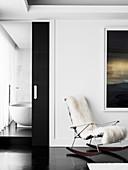 Desinger-Schaukelstuhl mit Felldecke vor Badezimmer-Schiebetür