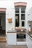 Arched, interior window in white, open-plan kitchen