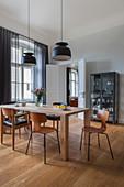 Designerstühle um den Holztisch im Esszimmer mit hellgrauer Wand