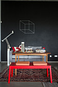 Red bench, wooden table and sofa against wall painted with chalkboard paint