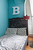 Letter B above child's bed with headboard painted with chalkboard paint