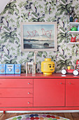 Red sideboard against jungle-patterned wallpaper in child's bedroom