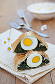 Two pieces of Easter strudel filled with spinach and egg