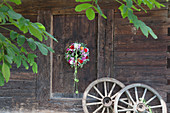 Door wreath of sage leaves, dahlias, phlox and green physalis husks next to old wooden wheels