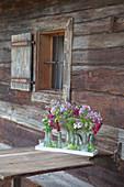 Kleine Flaschen mit Phlox, Jungfer im Grünen und Löwenmäulchen als Tischdekoration vor rustikalem Bauernhaus