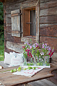 Phlox, love-in-a-mist and snapdragons in small bottles decorating table outside rustic wooden farmhouse