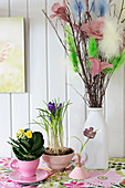 Kalanchoe and crocuses planted in teacups and vase of pussy willow decorated with feathers