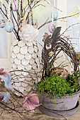 Birch wreath decorated with quail eggs and feathers in planted bowl in front of Easter eggs hung from branches in vase