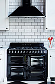 Black gas cooker and extractor hood on white subway wall tiles in kitchen