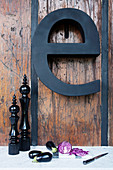 Black decorative letter on rustic wooden wall above vegetables and kitchen utensils on worksurface