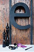 Schwarze Deko-Buchstabe an rustikaler Holzwand, im Vordergrund Arbeitsplatte mit Gemüse und Küchenutensilien